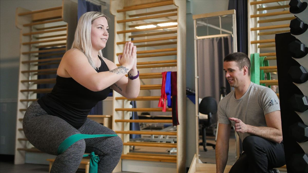 Doing Squads With Resistance Bands | Panorama Physio Clinic